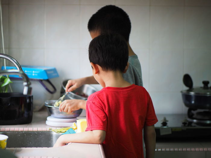 Quality time at home Baking Measuring Tool Child Childhood Males  Boys Real People Kitchen Home Lifestyles Indoors  Casual Clothing One Person Waist Up Kitchen Utensil Innocence Preparation  Siblings