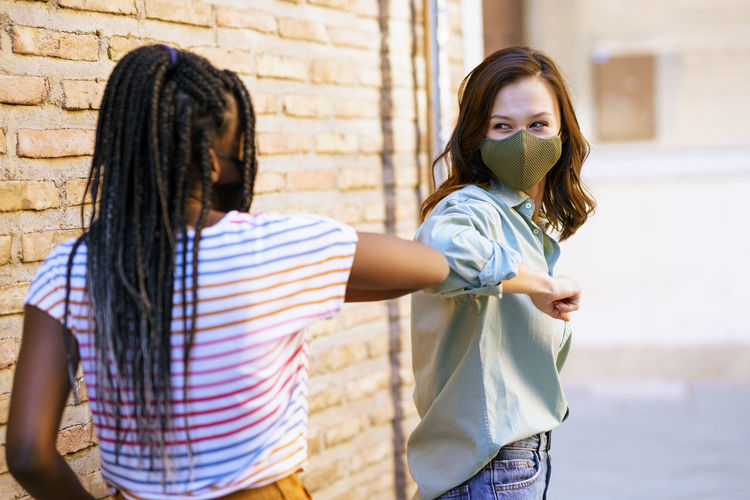 Smiling friends wearing mask doing elbow bump against wall