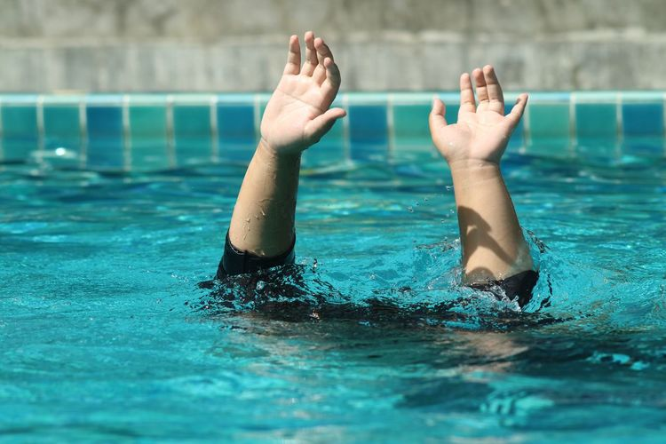 Cropped hands of boy standing in swimming pool