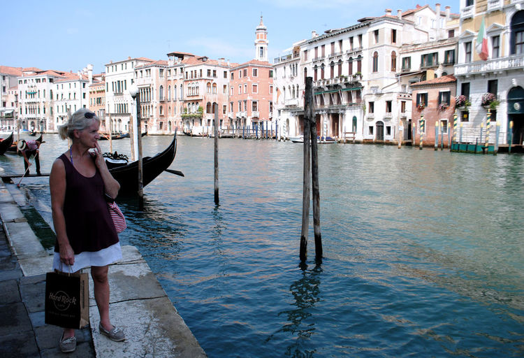 Woman standing by canal in city