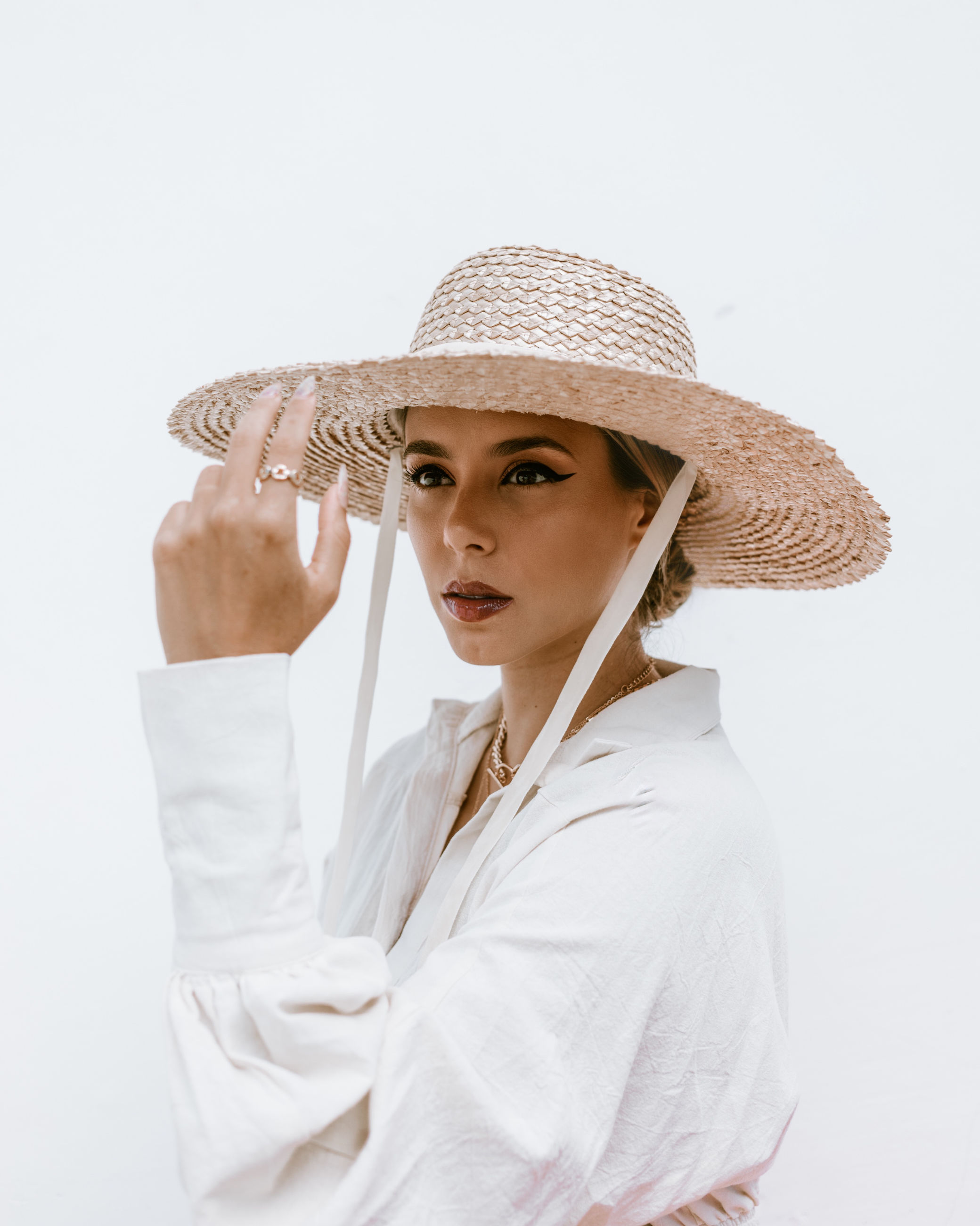 one person, hat, clothing, adult, portrait, women, sun hat, studio shot, waist up, indoors, cap, young adult, female, person, looking at camera, white background, straw hat, occupation, white, human face, fashion accessory, holding, looking, headgear, lifestyles, standing, fashion, spring