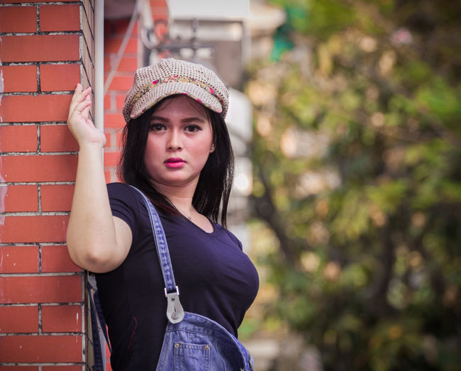 Portrait of beautiful young woman standing by brick wall