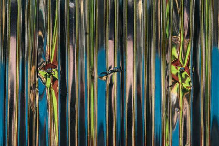 Full frame shot of abstract reflection on aluminum sheet fence
