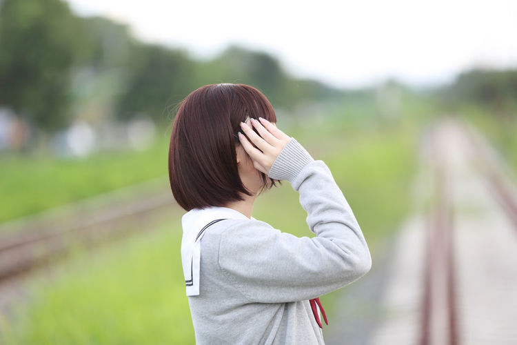 Young Woman In School Uniform Standing On Railroad Tracks