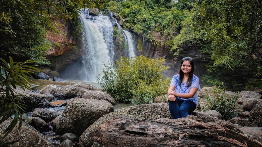 Portrait of woman sitting on rock against waterfall in forest