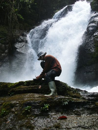 Man crouching on rock against waterfall