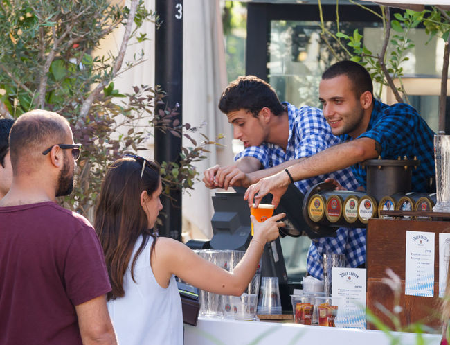Tel Aviv, Israel, September 16, 2016: The seller communicates with the guest of the festival at the annual beer festival in Tel Aviv, Israel Alcohol Annual Attractive Beer Celebration Clothes Costume Culture Dress Drink Event Festival Festive Folk Fun Glass Guest Happy Holiday Israel Mug Oktoberfest Smile Tel Aviv Traditional