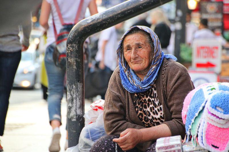 Senior woman looking away while sitting on street