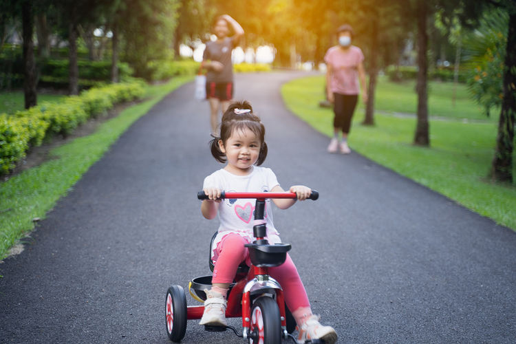 Portrait of cute girl riding bicycle on road