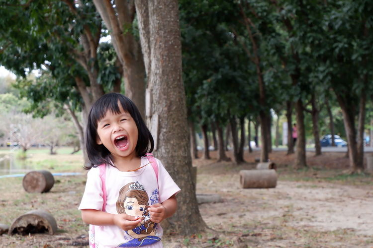 Cute girl laughing while standing against trees