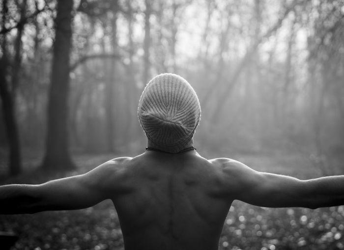 Rear view of shirtless man in forest