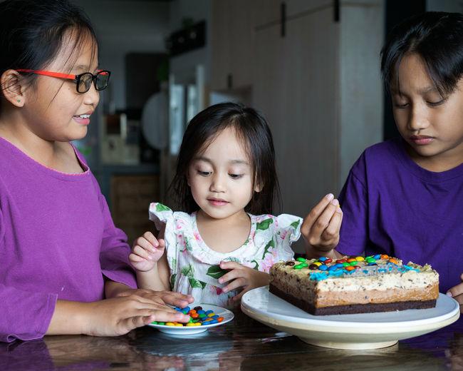 Cute siblings sitting by cake at home