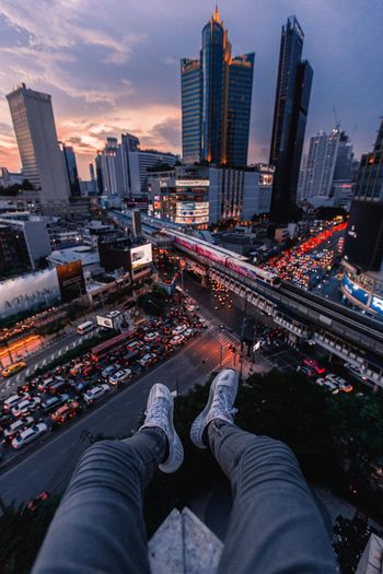 High angle view of person sitting on building terrace against cityscape at night