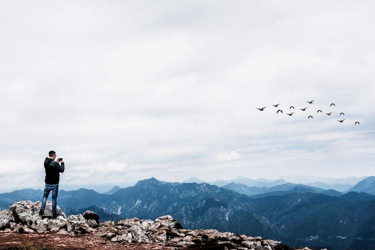 Full length of man photographing flock of birds