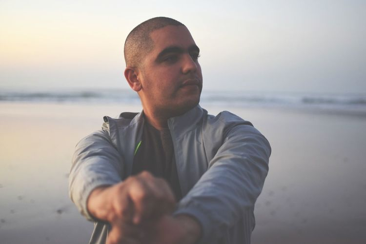 Thoughtful man standing at beach during sunset