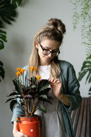 Cheerful woman with potted plants at plant store