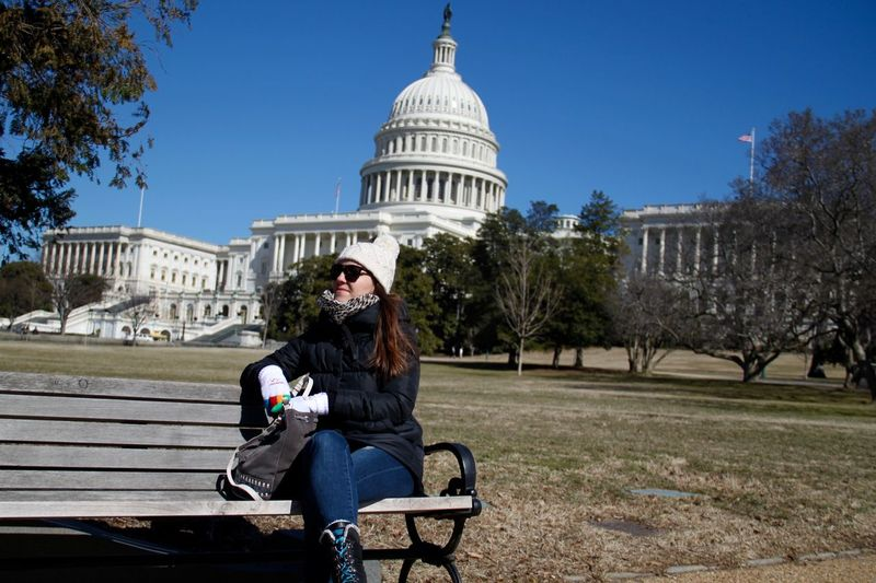 Young woman sitting on bench at park against state capitol building
