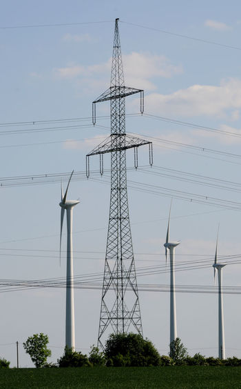 Wind turbines and electricity pylon against sky