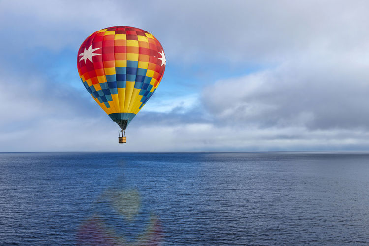 Hot air balloon over ocean Sky Sea Cloud - Sky Water Balloon Horizon Over Water Beauty In Nature Flying Hot Air Balloon Horizon Scenics - Nature Multi Colored Mid-air Transportation Adventure No People Outdoors Day Colorful Calm Water Pacific Ocean Conceptual Flying In The Sky Nature Red Yellow Color Blue