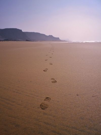 Footprints on sand at beach against sky