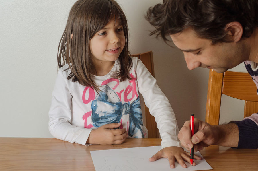 5 years girl doing educational exercises on a blank white paper Bonding Boys Child Childhood Day Education Elementary Age Family Family With One Child Girls Home Interior Indoors  Learning Lifestyles People Real People Sitting Table Togetherness Writing Young Adult This Is Family