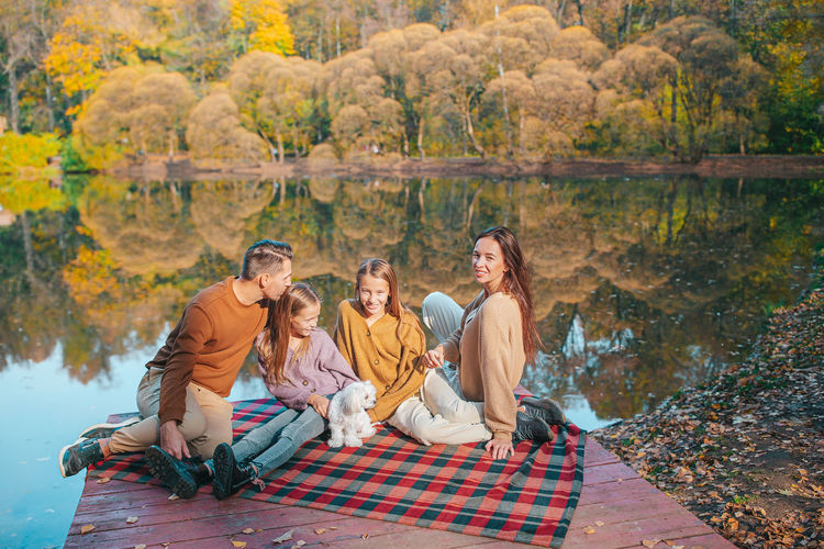 Group of people sitting in autumn forest