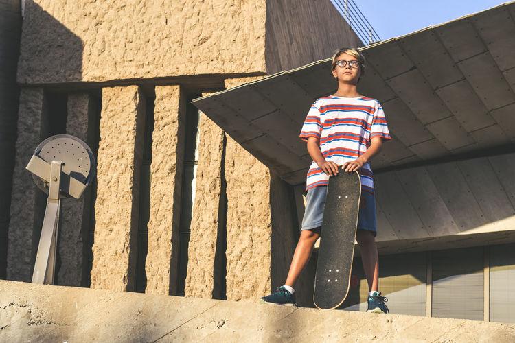 Full length of boy holding skateboard while standing outside building