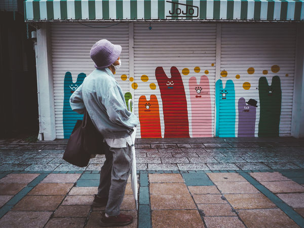 Architecture Building Building Exterior Built Structure Creativity Day Footpath Full Length Human Representation Lifestyles Multi Colored One Person Real People Rear View Religion Representation Traditional Clothing Walking Wall - Building Feature