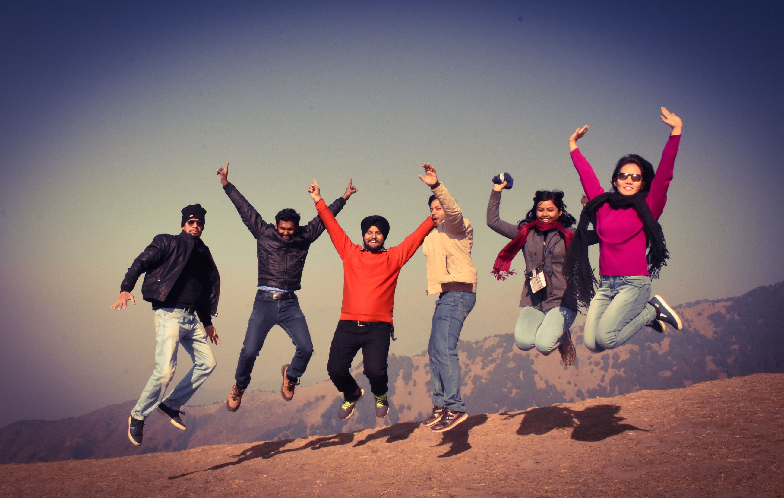 sky, full length, leisure activity, happiness, emotion, real people, togetherness, friendship, lifestyles, men, enjoyment, jumping, mid-air, clear sky, group of people, nature, land, human arm, fun, sand, positive emotion, limb, arms raised