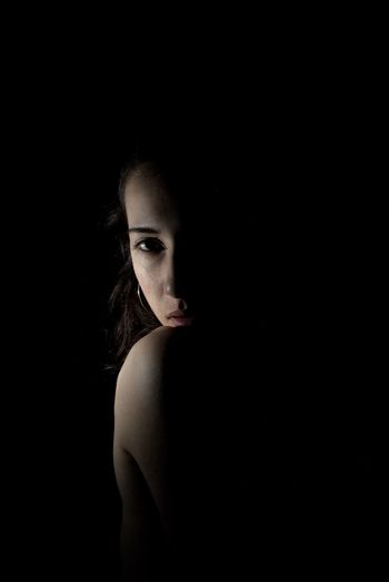 Portrait of topless young woman against black background