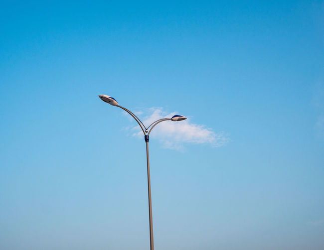 Low angle view of bird perching on street light against clear blue sky
