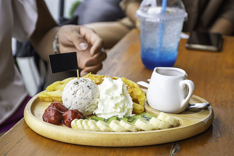 Sweet water pour on the waffle with ice cream and fruits including bananas, kiwi and strawberries in wooden plate on table. Baked Bakery Banana Berry Black Brown Cake Chocolate Cream Crispy Cuisine Delicious Dessert Dish Eat Food Fresh Fresh Cream Fruit Fruits Golden Health Honey Ice Ice Cream Kiwi Fruit Meal Pastry Plate Red Salad Snack Strawberries Strawberry Sugar Summer Sweet Syrup Table Tasty Top Traditional Vanilla Vegetarian Wafer Waffle Waffles White Wooden Wooden Table
