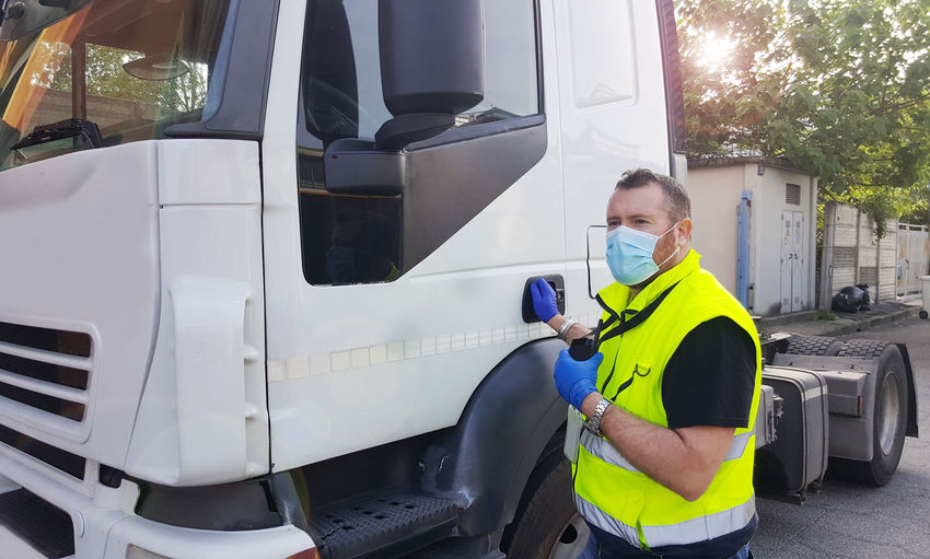 Man wearing mask standing by truck