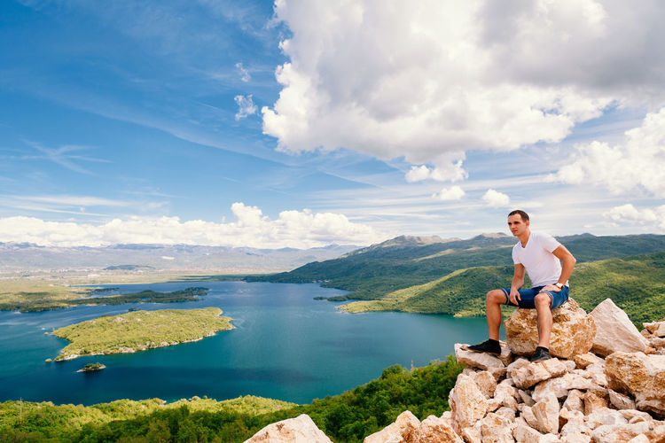 Man sitting on rock at lake against sky