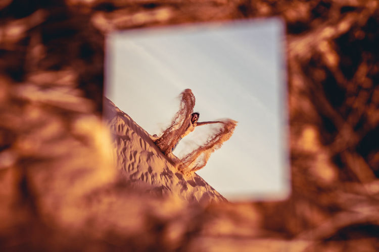 Reflection of woman spilling sand in mirror