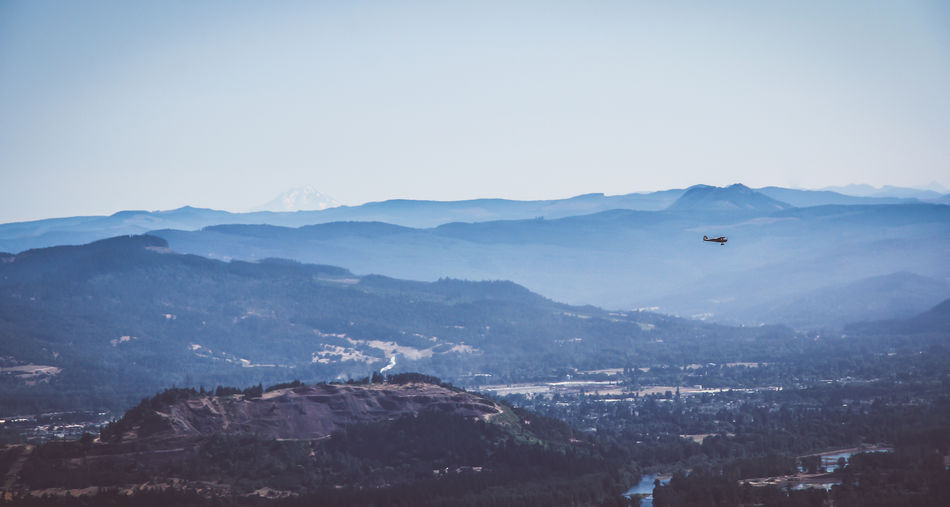 Scenic view of helicopter flying over mountains against clear sky