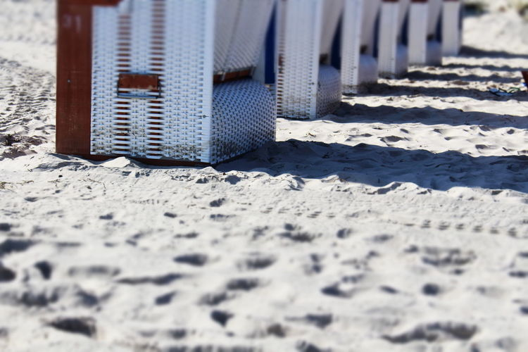 Cropped Image Of Hooded Beach Chairs On Sand