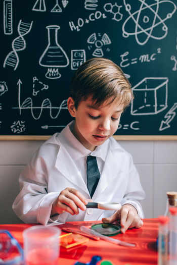 Boy Wearing Lap Coat While Sitting In Classroom
