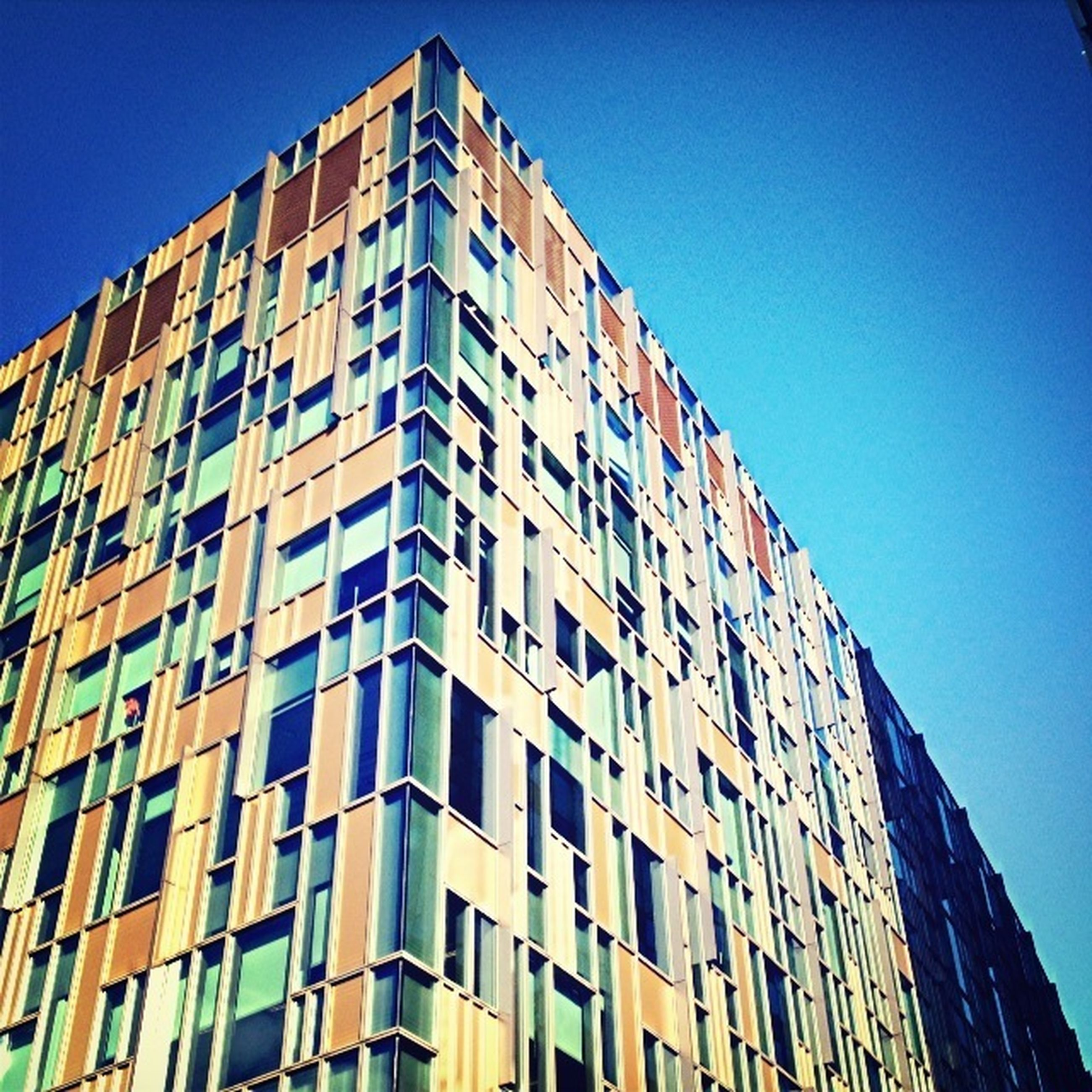 building exterior, architecture, built structure, low angle view, window, clear sky, city, building, blue, residential building, apartment, residential structure, modern, office building, balcony, outdoors, sky, city life, day, no people