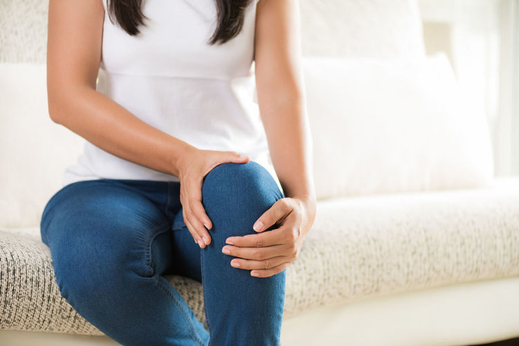 Midsection of woman suffering from knee pain while sitting at home