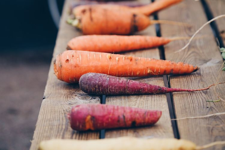 High angle view of purple and orange carrots laying on a wooden table outdoors