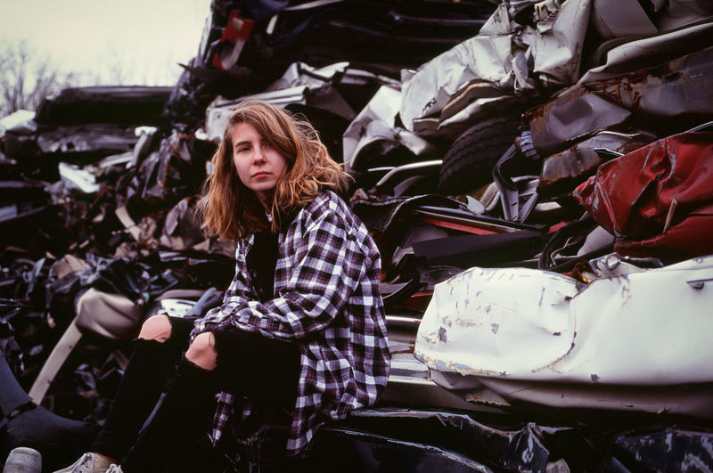 Young woman sitting in an auto salvage yard