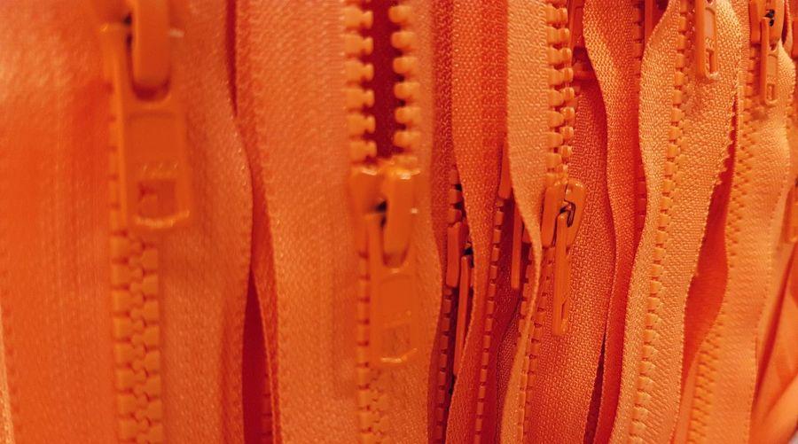 Full frame shot of orange zips