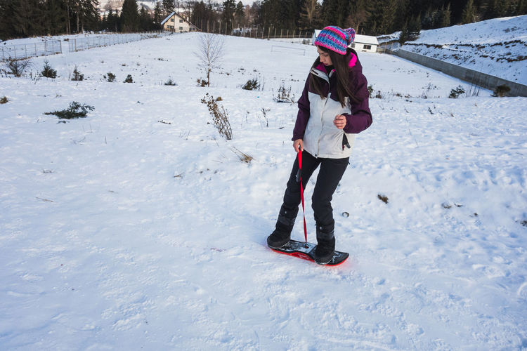 Woman learning how to ride on a board slide Cold Temperature Winter Snow Warm Clothing Real People Clothing One Person Leisure Activity Sony Rx100 Outdoors Extreme Weather Covering White Color Day Nature Women Board Board Slide Slide Board Slide Sliding Hat Winter Wintertime Holiday