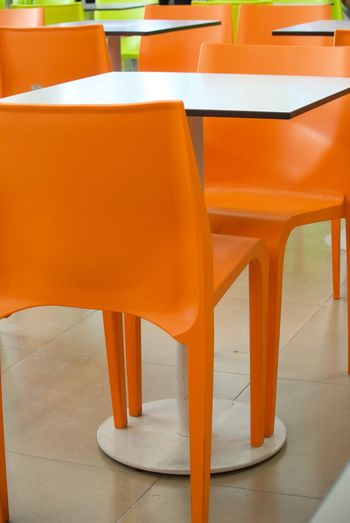 Seat Chair Table Orange Color Furniture Empty Absence Indoors  Restaurant Business No People Cafe Food And Drink Flooring Wood - Material In A Row Arrangement High Angle View Yellow Day Setting Tiled Floor Orange Cafeteria