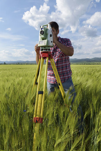 Land surveyor in a wheat field working with total station. Geodesy measurements Industry Sunny Wheat Working Agriculture Caucasian Cloud - Sky Day Engineer Equipment Field Geodesy Internet Land Surveyor Location Measurement Network One Man Only Outdoors Point Professional Occupation Technology Tripod Wireless Technology Young Adult