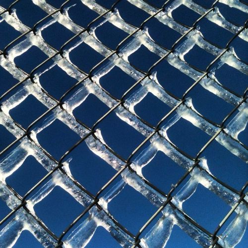 Full frame shot of chainlink fence covered with ice against blue sky