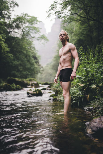 Full length of shirtless man standing in water at forest