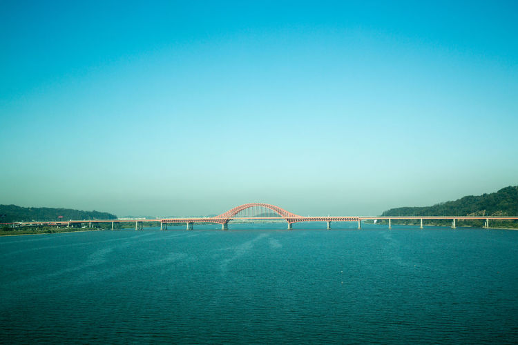 Bridge Over Sea Against Blue Sky