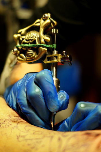 Tattoo Tattoos Indoors  Selective Focus Metal Human Hand Human Body Part Focus On Foreground Blue Hand Close-up Arts Culture And Entertainment Holding Art And Craft One Person Real People Human Representation Gold Colored Artist Creativity Musical Instrument Finger Tattooed Sashalmi Art